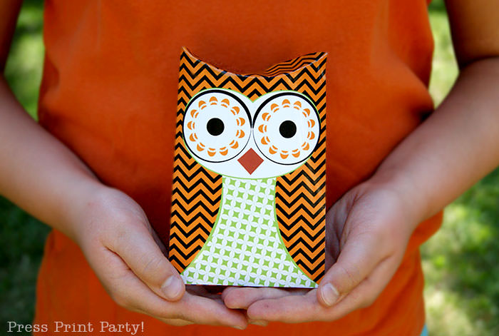 Free printable owl halloween treat boxes, favor bags, Orange, purple and green. Girl with orange shirt holding 2 owl pillow boxes by Press Print Party!