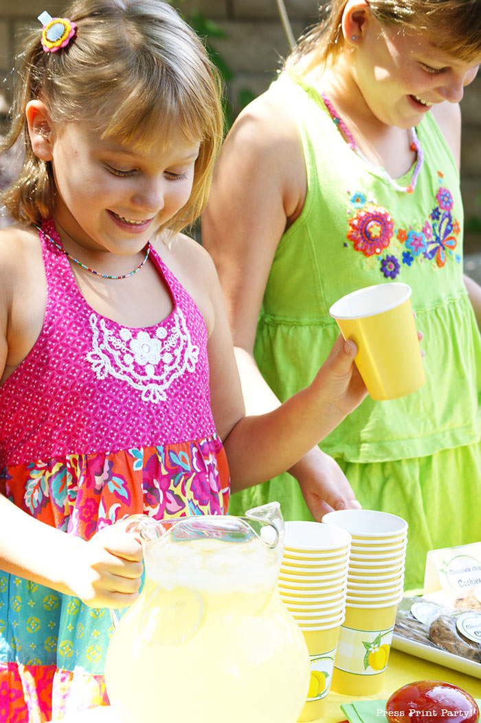Girls with a lemonade stand. with lemonade banner price list and labels and cupcake wrappers. free printables Press Print Party!