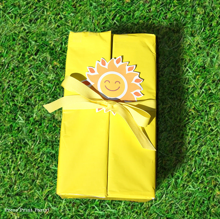 Closed yellow box on grass with happy sun tag