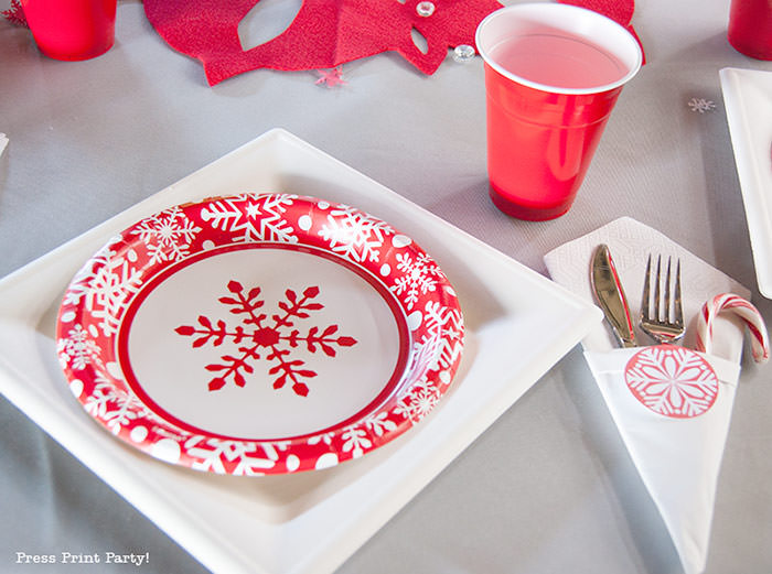 DIY Christmas Centerpiece Ideas red snowflake red and white christmas paper plates with red cup. grey tablecloth.