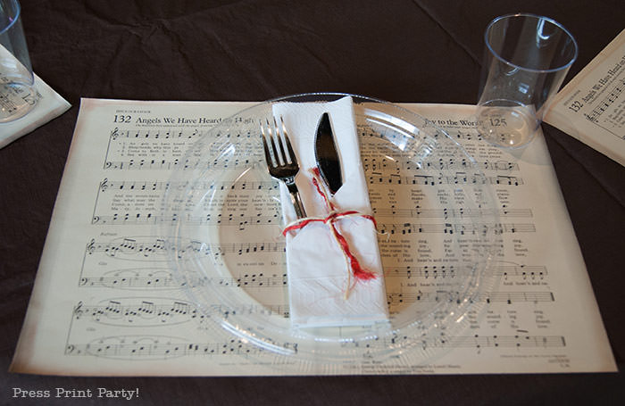 Table setting in white napkin with rafia. Rustic Christmas table centerpiece with greenery, rustic owl, white mason jar, pinecones, and berries. With a free music sheet table number printable download. With a brown tablecloth and music sheet place mats. Easy and cheap. by Press Print Party!