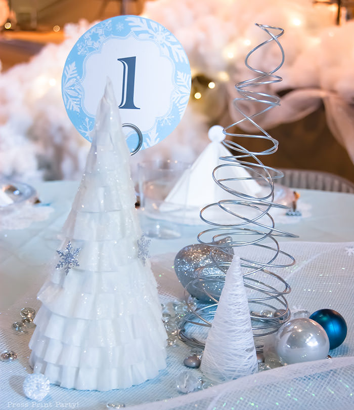 coffee filter tree with snowflake confetti For Christmas table decor ideas blue and silver winter wonderland decorations. Christmas tablescape for large event christmas party, diy holiday table setting. by Press Print Party!