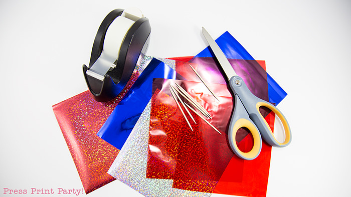 Cellophane paper, scissors, toothpicks and tape for tassel cupcake toppers.