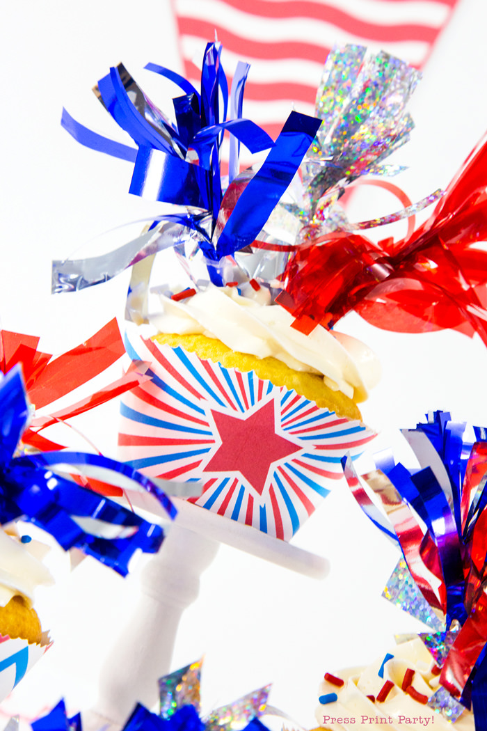 Patriotic cupcake wrapper with red star and 3 tassel toppers in red silver and blue.