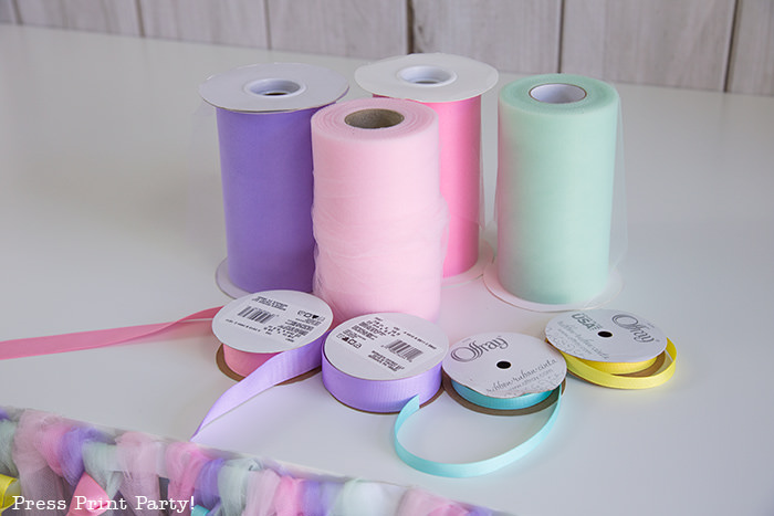 4 tulle rolls on table with 4 ribbons to make a tulle table skirt