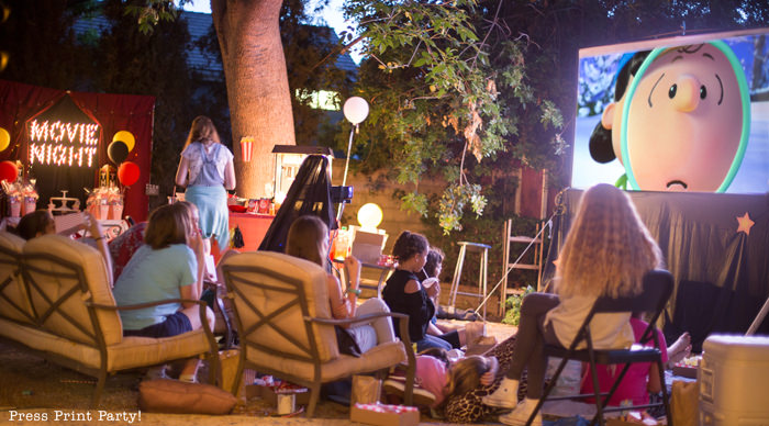 kids watching a movie at a backyard movie night - Press Print Party!