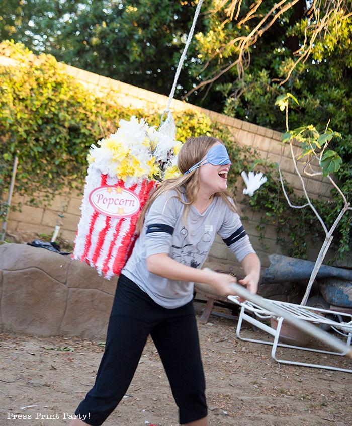 Girl hitting a popcorn box pinata - Press Print Party!