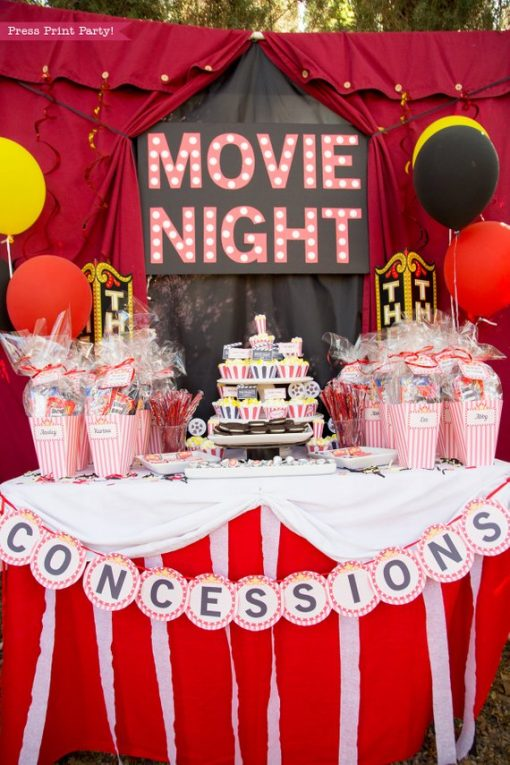 Movie NIght party table with marquee letters and popcorn box favors