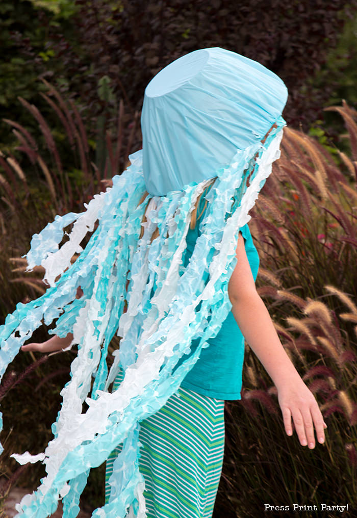 Girl with jellyfish costume for Halloween. Blue and white tentacles. Press Print Party!
