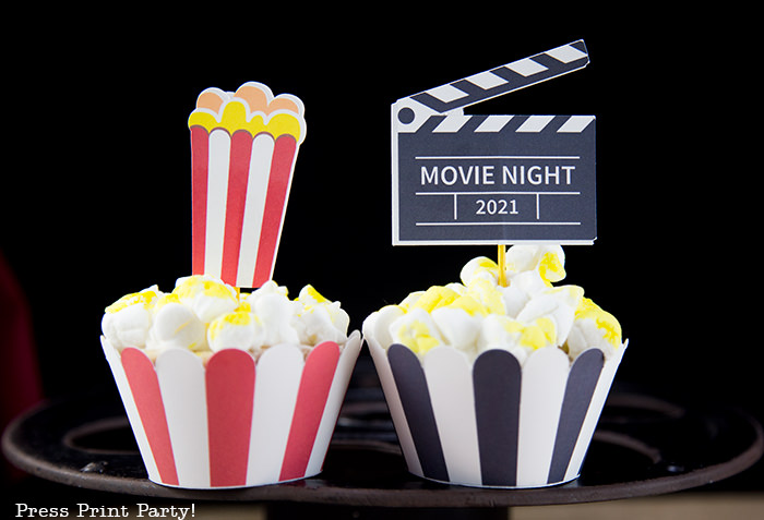 2 popcorn cupcakes. One with a red and white wrapper, one with a black and white wrapper. - Press Print Party!
