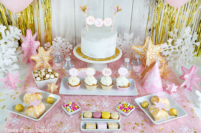 winter onderland first birthday girl party pink and gold dessert table with onederland cake and cupcakes, printable snowflakes, favor boxes and chocolate - Press Print Party!