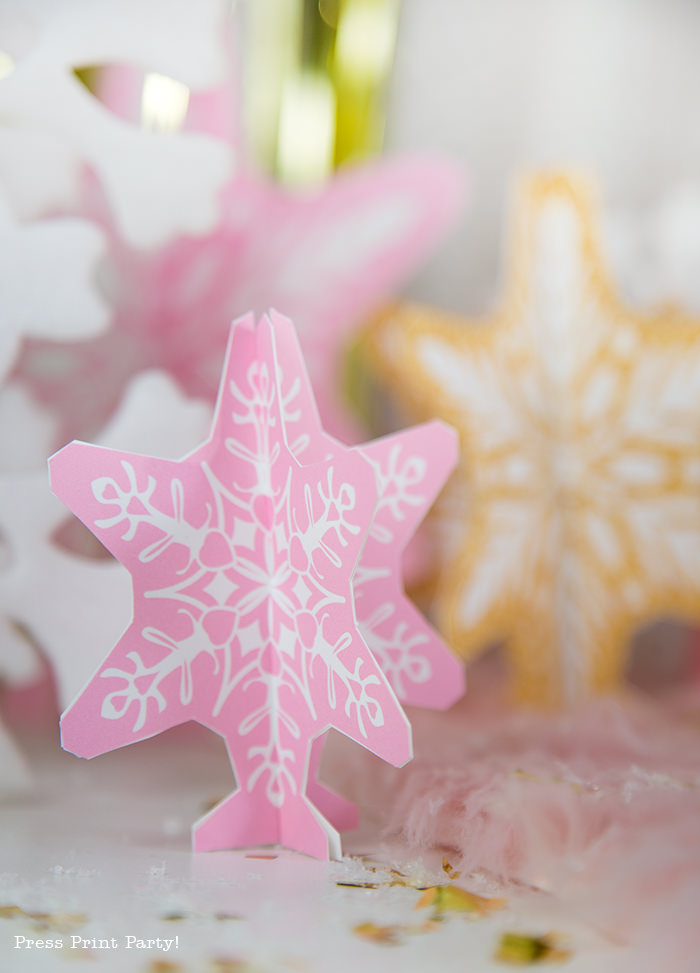 Printable 3D snowflakes in pink and gold for a girl onederland party winter onederland gold and pink snowflakes kisses with printable labels winter onderland first birthday girl party pink and gold dessert table with onederland cake and cupcakes, printable snowflakes, favor boxes and chocolate - Press Print Party!