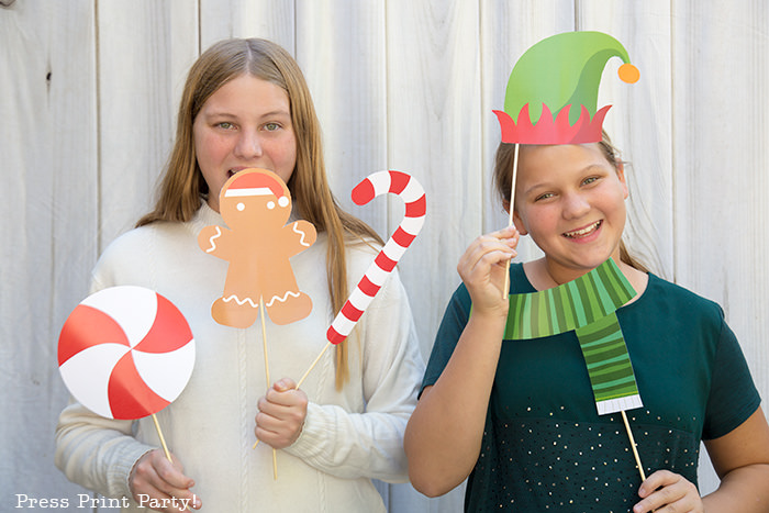 2 girls with Christmas photo booth props. one with a gingerbread man and candy cane, the other with elf hat and scarf - Press Print Party!