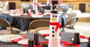 snowman made with cans on christmas table with snowman made with plates on black tablecloth - Press Print Party!