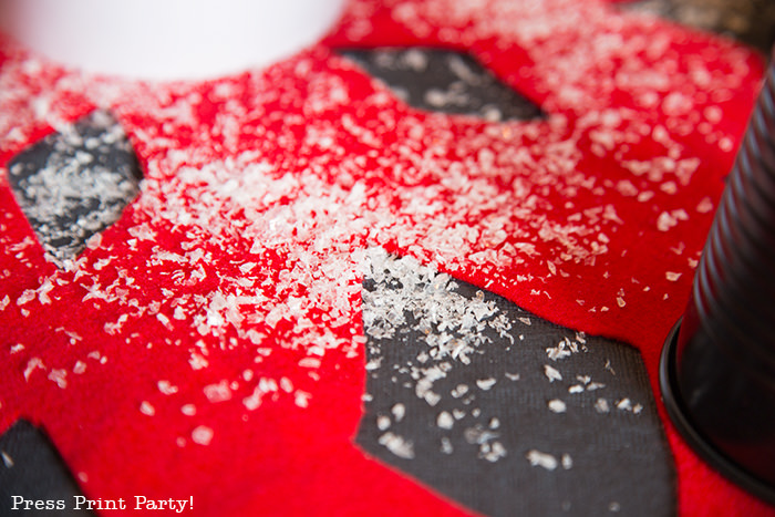 close up of red felt snowflake table centerpiece with snow on black tablecloth - Press Print Party!