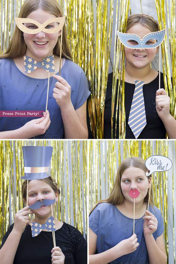 Girls holding New Year's photo booth props with hat, bowtie, mustaches and kiss me sign - Press Print Party!