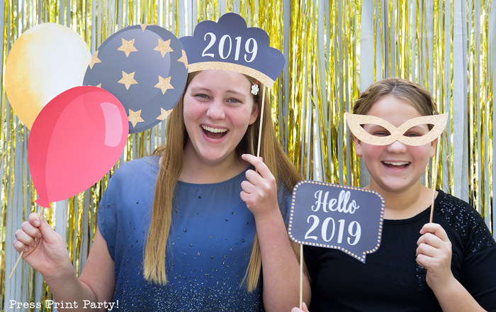 2 girls having fun with new year's eve photo booth props. 2019 tiara and speech bubble, balloons and mask. Press Print Party!