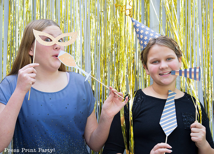 2 girls having fun with new year's eve photo booth props. party hat, noise maker, champagne glass, mask - Press Print Party!