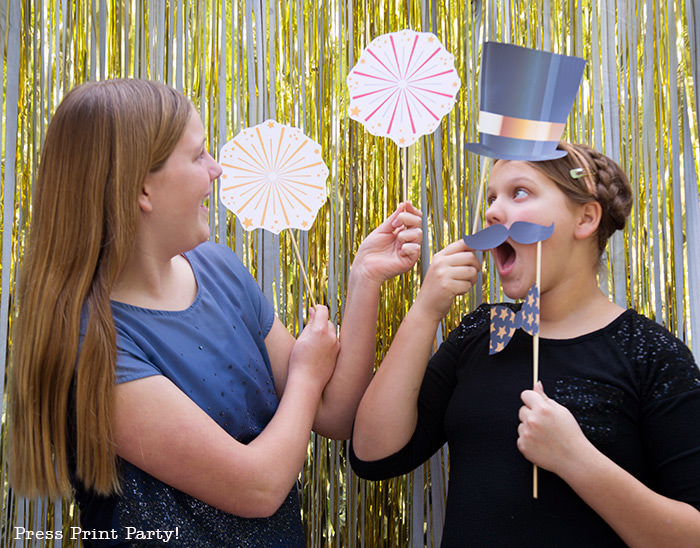 2 girls having fun with new year's eve photo booth props. hat, mustache and fireworks- Press Print Party!