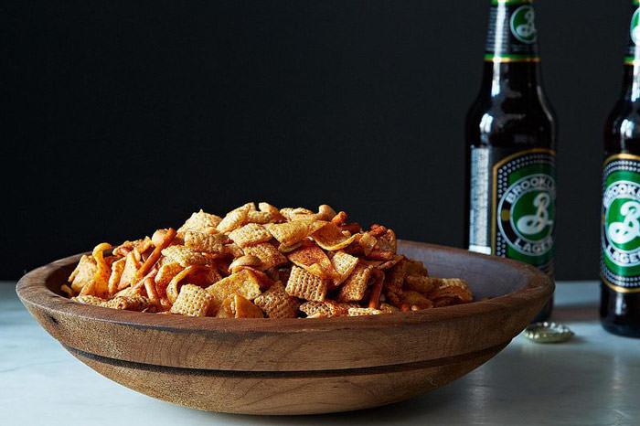 DIY chex snack mix in a wooden bowl with beer in the back