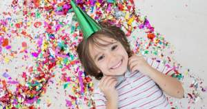 The secret to getting RSVPs to your kid's birthday party - smiling kid with birthday hat - Press Print Party!