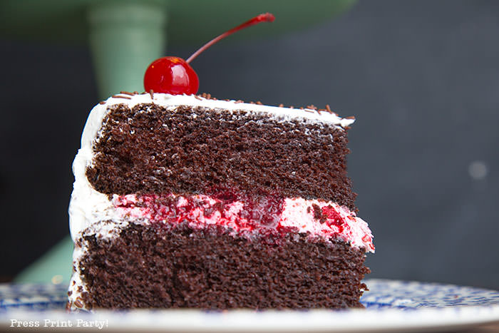 Cut piece of chocolate cake with white frosting and berry filling and a cherry on top - Press Print Party!