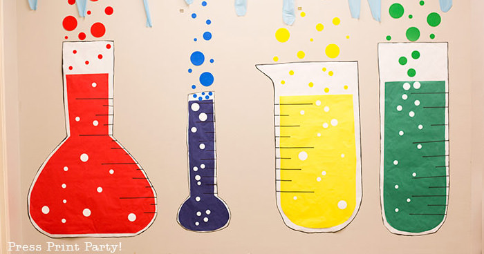 4 giant paper beakers for science party decorations wall backdrop. red, blue, yellow and green with bubbles