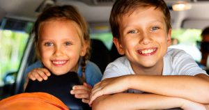 2 kids laughin in car with games to play in the car
