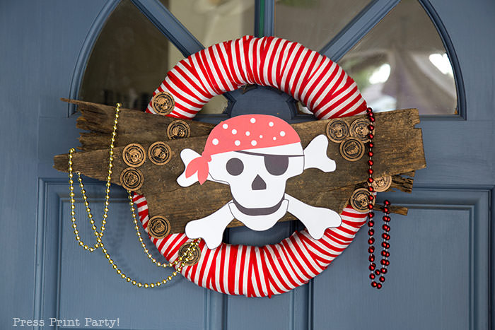 Halloween wreath pirate wreath diy with pirate coins and red and white striped fabric. free pirate skull and crossbone printable - Press Print Party!