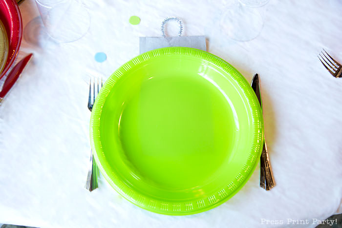 close up of green plate with silver napkin to look like an ornament. Christmas tablescape balloon centerpiece decoration with large ornament balloons and plates that look like ornaments. Very cheery and bright. Fun and creative for your Christmas party. Simple Christmas balloon decor ideas diy. Press Print Party!