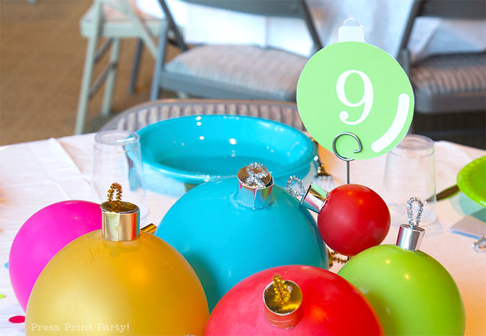 close up of large ornament christmas centerpiece with ballons. with table number 9. Balloons with ornament toppers in green, gold, blue, red and hot pink. Christmas tablescape balloon centerpiece decoration with large ornament balloons and plates that look like ornaments. Very cheery and bright. Fun and creative for your Christmas party. Simple Christmas balloon decor ideas diy. Press Print Party!