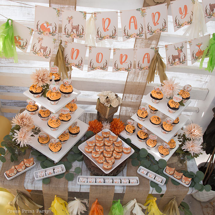Woodland baby shower dessert table with cupcakes towers and fox macarons. woodland printable banner with cute fox and deer. Woodland animals Baby Shower Theme with woodland creatures and forest animals party supplies. Woodland decoration girl baby shower ideas. Can be used for woodland birthday party. Rustic forest animals with flowers and antlers. Fox baby shower, Deer baby shower.