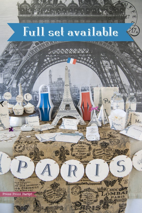 Paris Party theme decorations desert table with paris party printables. Eiffel tower backdrop and centerpiece with cupcakes and french flag. Vintage French Party decorations and treats. With Paris banner and red whit and blue balloons. Press Print Party!