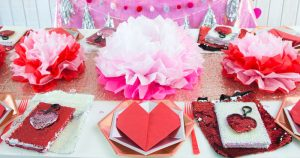 Galentine's Day table with sequins table runner, tissue paper flower, heart napkins hexagonal plates. flip sequins favors - Press Print Party!