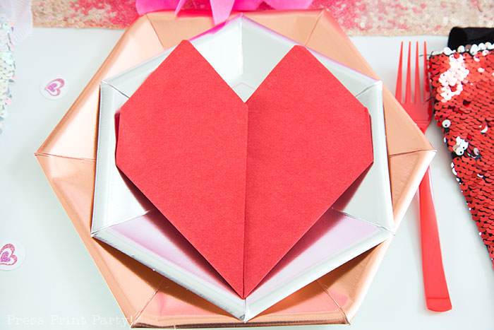 Red heart napkin fold on rose hexagonal metallic plate and silver plate - Galentine's Day Party Ideas for Teens - Press Print Party!