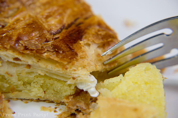 Authentic galette des rois recipe - Piece on a plate with a feve and a fork.French kings cake pastry with almond paste. French tradition, French style kings cake. easy to make with golden crown and feve by Press Print Party!