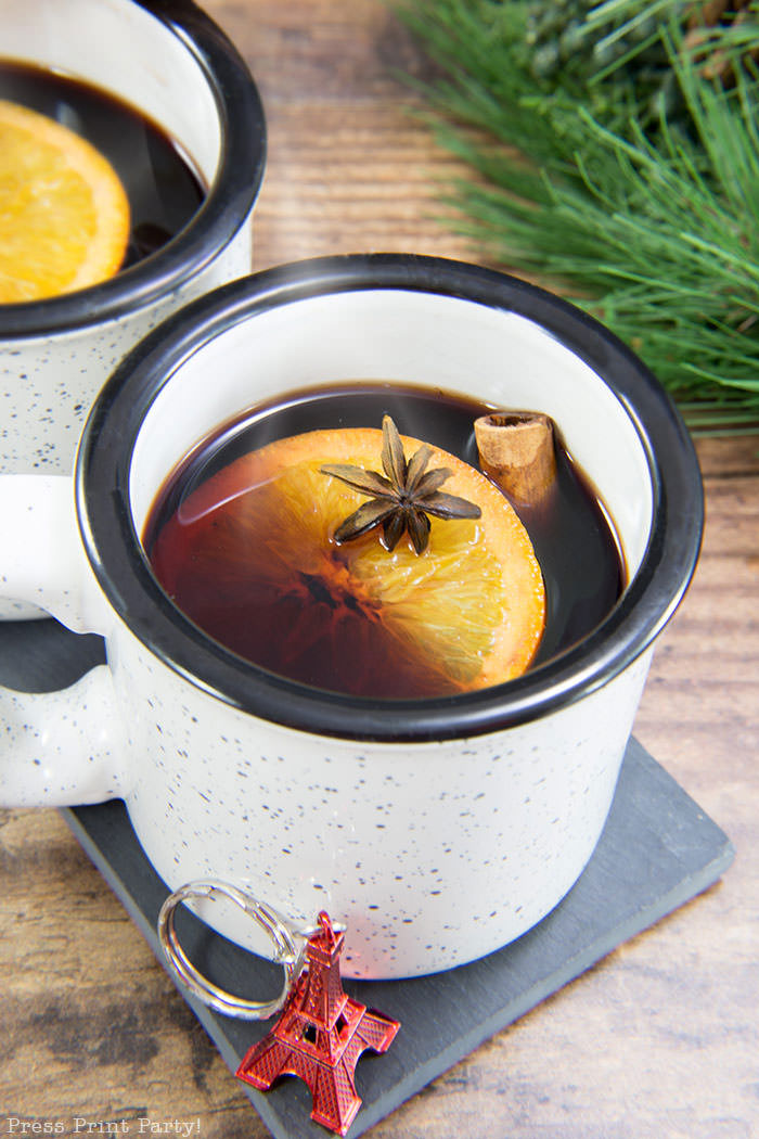 French Vin Chaud, Mulled wine recipe . white cup with hot wine, orange, cinnamon stick, and star anis. Straight from the streets of Paris. Press Print Party!