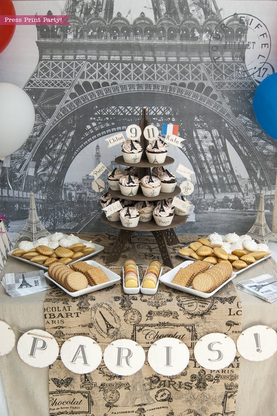 Paris Party Paris Party theme decorations desert table with paris party printables. Eiffel tower backdrop and centerpiece with cupcakes and french flag. Vintage French Party decorations and treats. With Paris banner and red whit and blue balloons. Press Print Party!