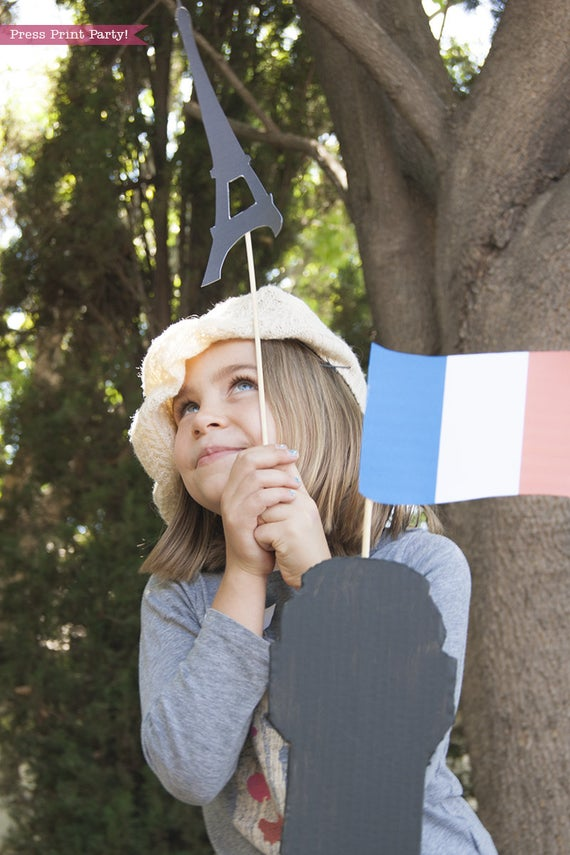 Girl with Paris photo booth props on top of cardboard Eiffel tower with french flag and beret. Press Print Party