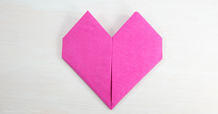Heart Fold Napkin instructions- How to fold a napkin like a heart - paper napkin or cloth napkins - By Press print Party. Pink paper napkin folded like a heart DIY tutorial