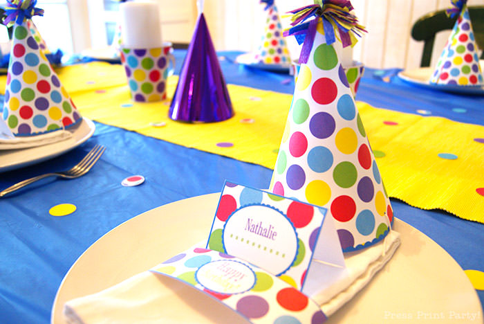 5 ways to make your kid's birthday special at home. Celebrate at home with family Press Print Party. Birthday party decorations on table with party hat colorful dots