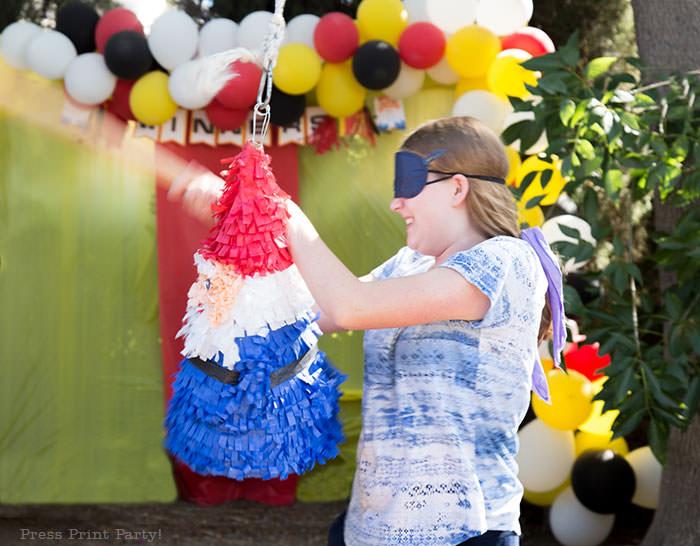 Girl hitting pinata. The amazing race party ideas - Roaming gnome pinata DIY - Press Print Party!