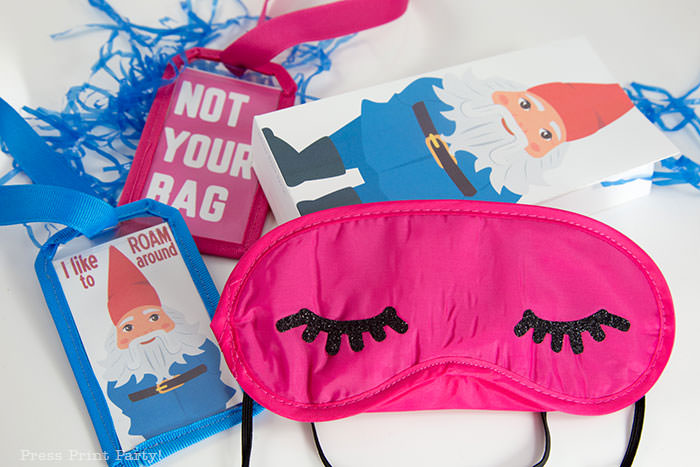 Amazing Race Party Favor Bags with sleep mask with eyelashes and 2 luggage tags, one with a roaming gnome that says I like to roam around and one with Not Your Bag in pink. Press Print Party!
