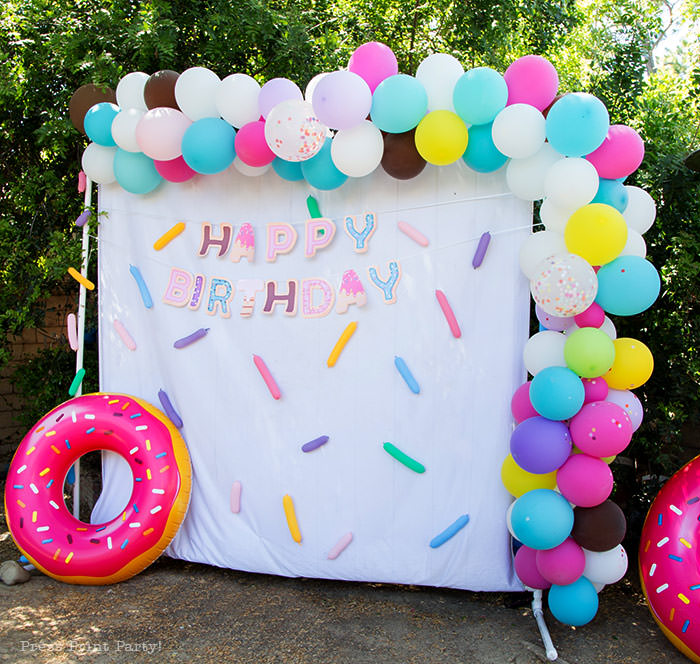 Donut party ideas donut photobooth with balloon garland and happy birthday banner and confetti. Press Print Party