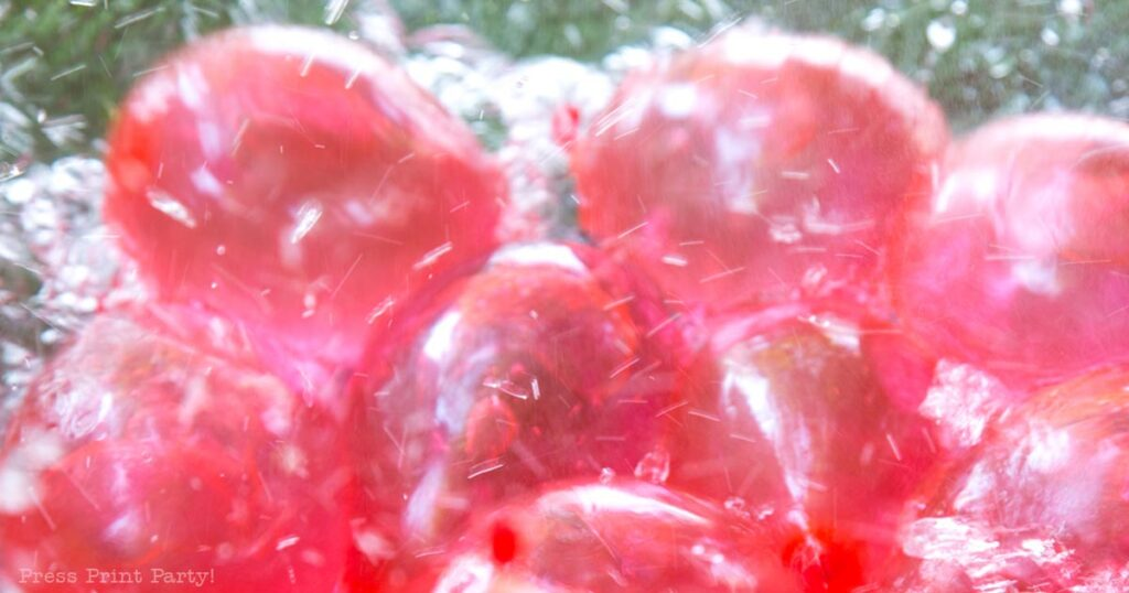 15 best competitive water balloon games for teens, kids, youth activities. Red water balloons in bowl. Press Print Party